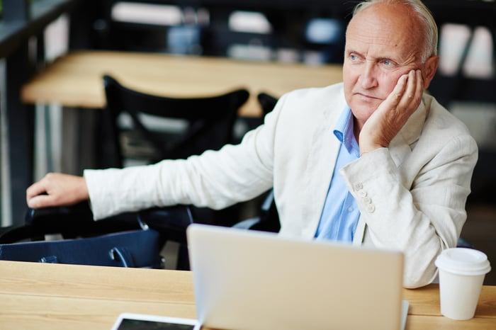 Older man sitting at table thinking.