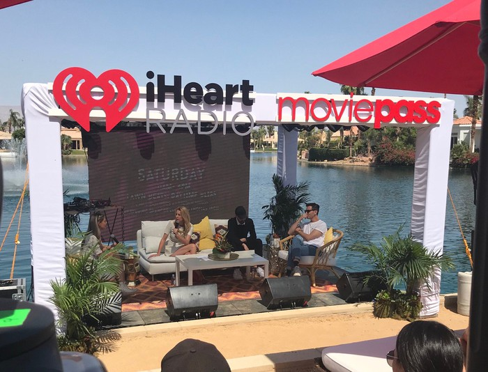 Four people sitting on a couch on a stage to promote MoviePass and iHeart Radio at a film festival.