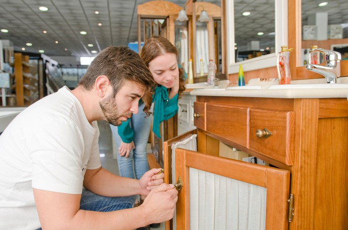 A couple examining a bathroom sink cabinet at a store