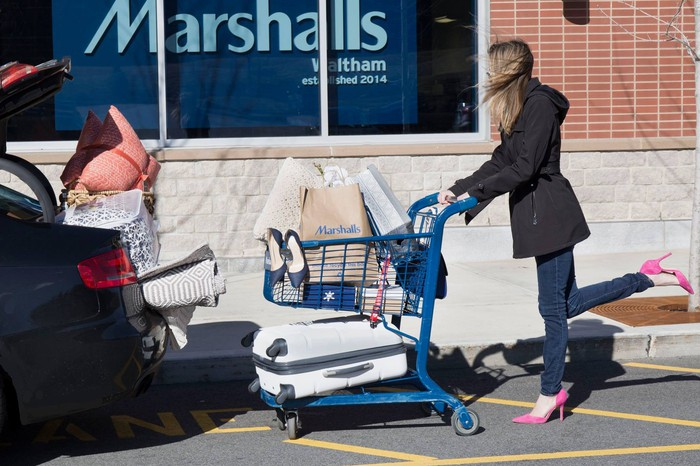 A woman pushing a merchandise-filled cart outside of a Marshalls store