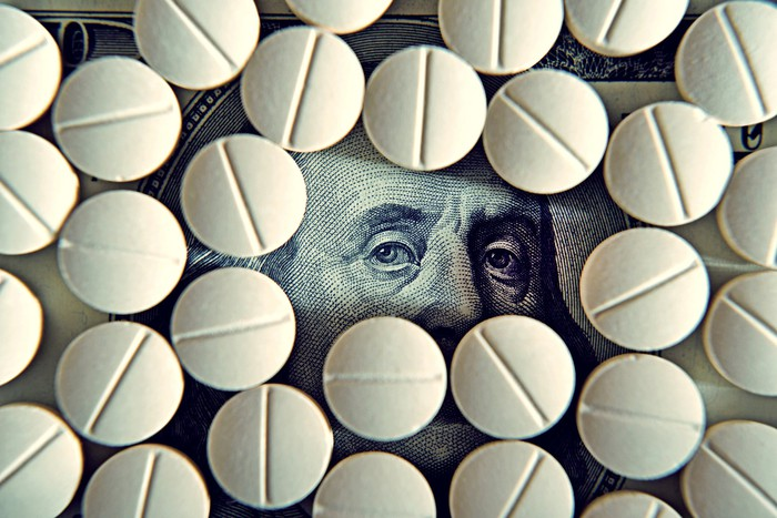 Pills on top of a one hundred dollar bill with Ben Franklin's eyes peaking through.