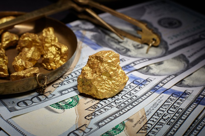 Gold nuggets on top of U.S. hundred-dollar bills.