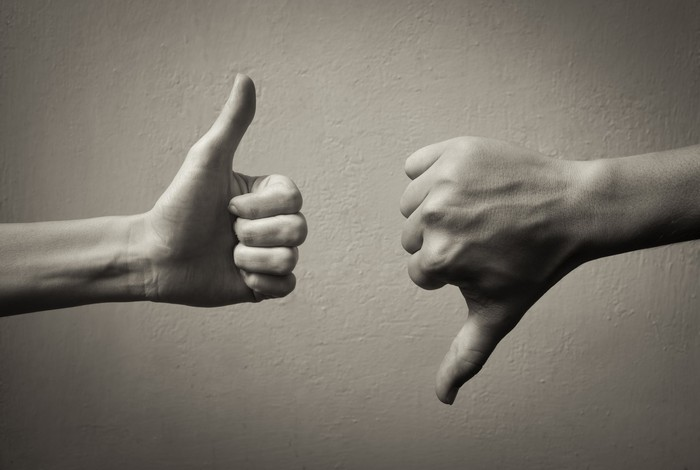 two hands in black and white, one giving a thumbs up sign, the other thumbs down