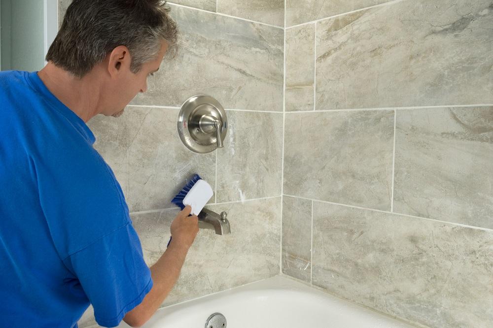 Installer using a brush on tile in bathroom.