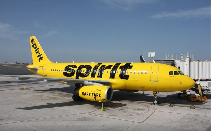 A yellow Spirit Airlines A319 jet parked at an airport gate.