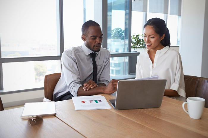 Professionally dressed man and woman looking at a laptop
