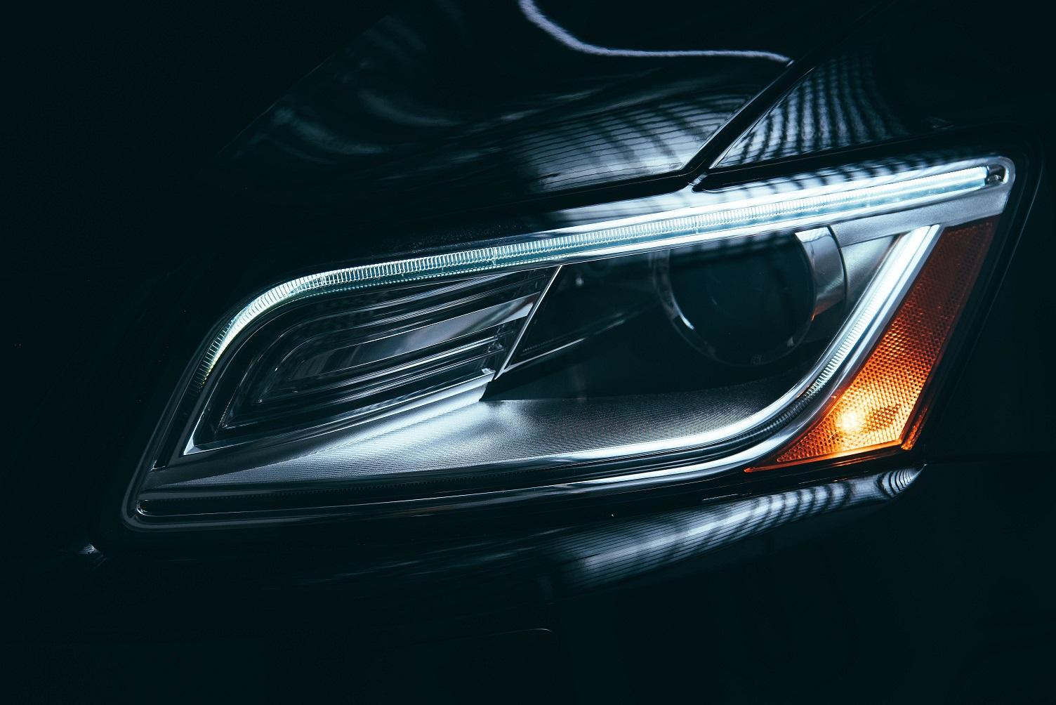An extreme closeup of the acute angle of a headlight.