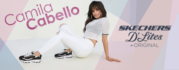 The singer Camila Cabello in a Skechers ad, wearing a pair of casual athletic shoes, white pants, and white shirt.