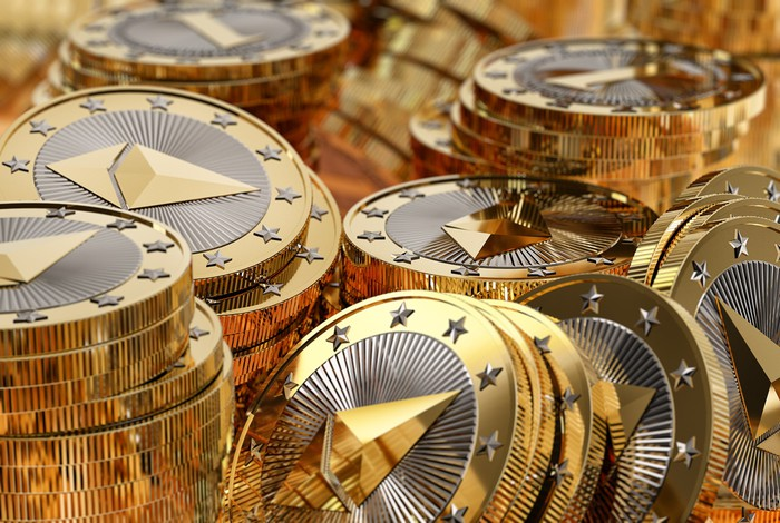 Messy stacks of physical silver and gold Ether coins.