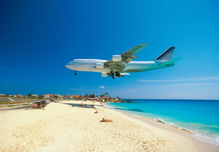 Airplane coming in for a landing just above the sunny beaches of St. Maarten.