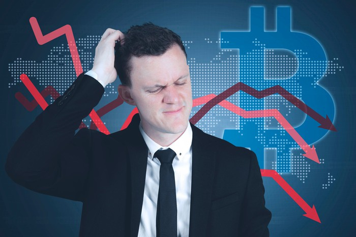 Businessman looks confused in front of screen featuring arrows downward and a bitcoin symbol.