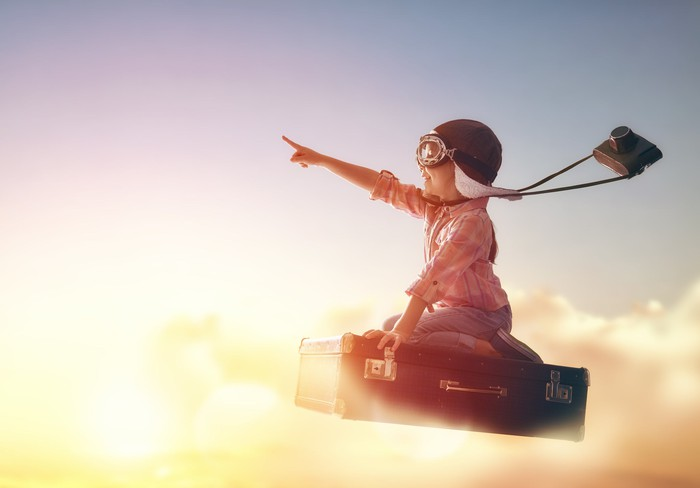 A little girl in an aviator hat and goggles pointing higher as she rides a suitcase through the sky.