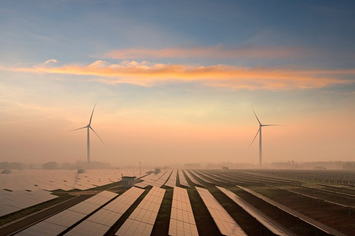 Solar panels spread out over the horizon with wind turbines in the distance.