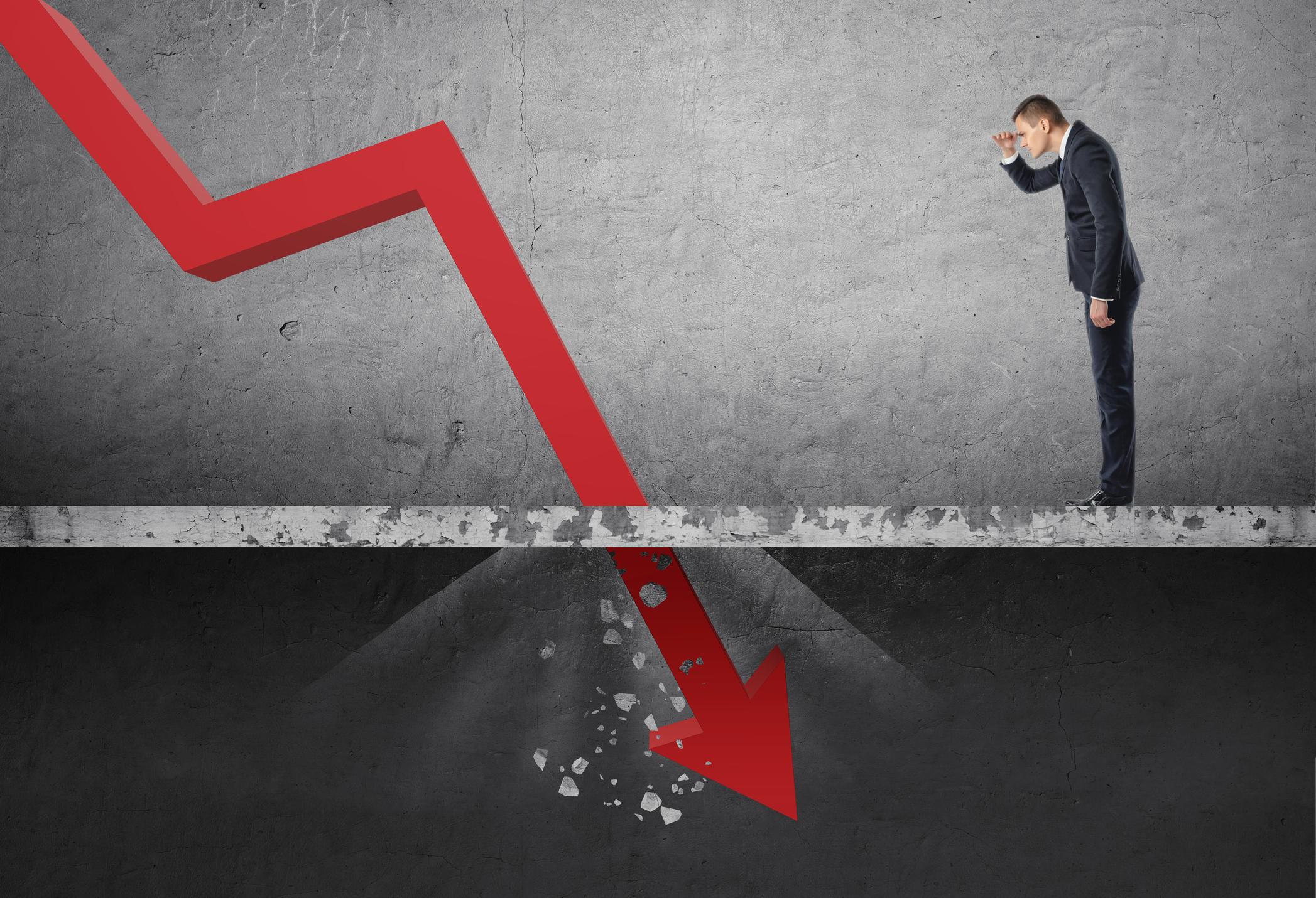 A businessman watches a stock chart crash.