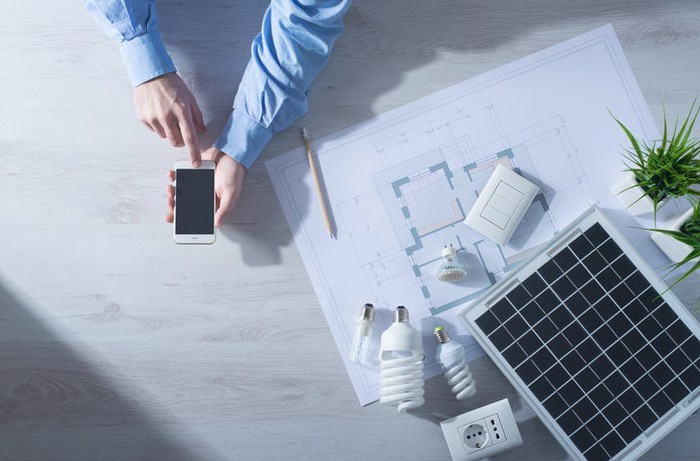 A man sitting at a desk with blueprints for a rooftop solar system and he's on his smartphone.