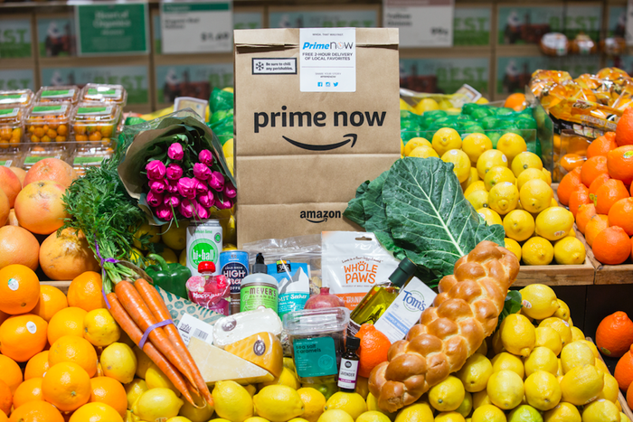 An Amazon-branded grocery bag sits atop a pile of fruits and other popular items found at Whole Foods