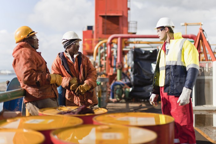 Three rig workers wearing hard hats talking to each other during a break