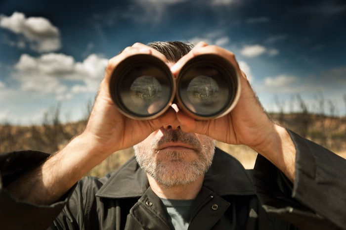 a ma looking through a pair of binoculars