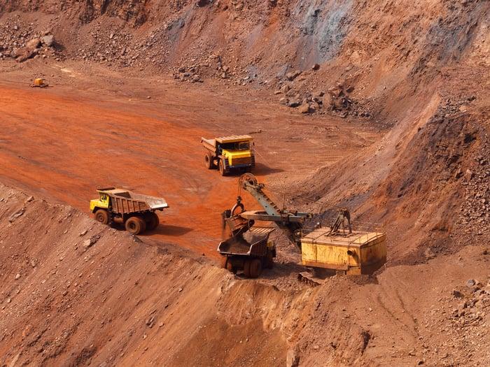 Excavator loading trucks in an iron ore mine.
