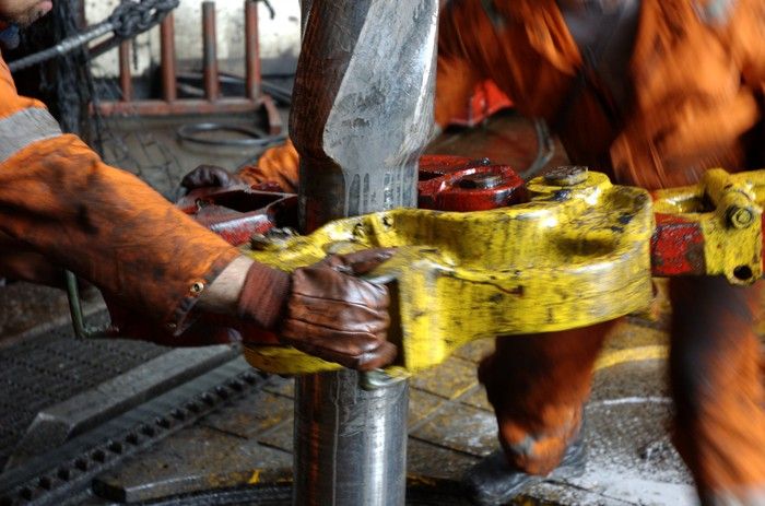 Rig workers fitting a pipe.