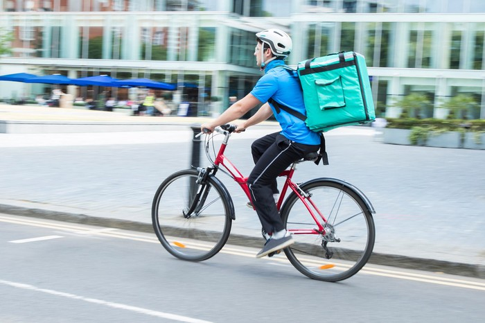 Man riding on bike with food delivery bag on his back.