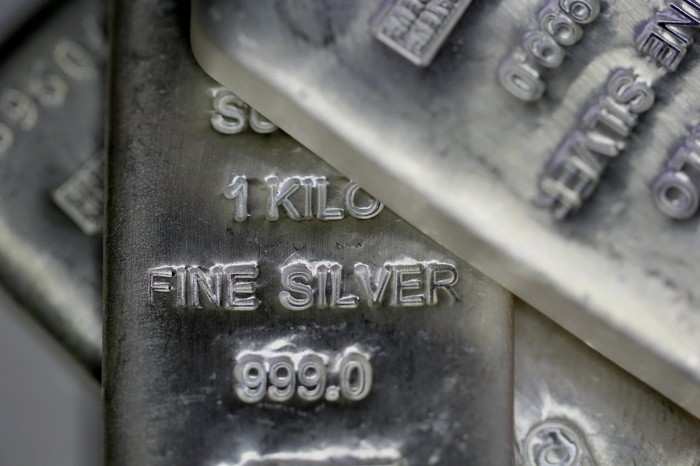 Several kilo-sized silver bars piled on top of each other.