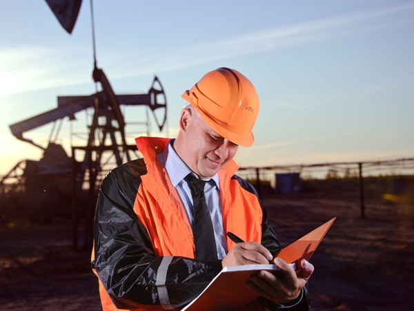 16_06_15 Man with notebook in front of oil well_XOM_BP_TOT_E_RDSB_CVX_GettyImages-156525694