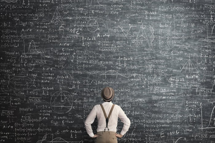 Man standing in front of a chalkboard with equations and charts on it.