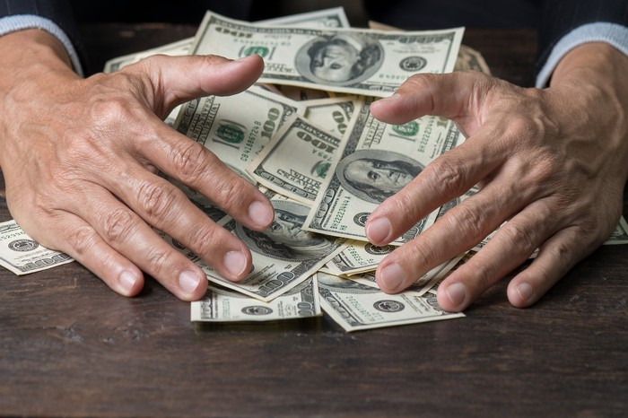 A man's hands sweeping a pile of hundred dollar bills across a table.
