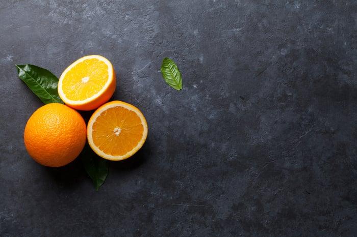 Three sliced oranges on a dark gray surface.