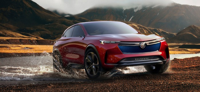 The red Buick Enspire concept is shown in rugged mountainous surroundings, appearing to have just emerged from a stream.