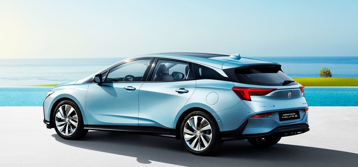 A rear three-quarter view of a blue Buick Velite 6, a station-wagon-like vehicle, on a beachfront.