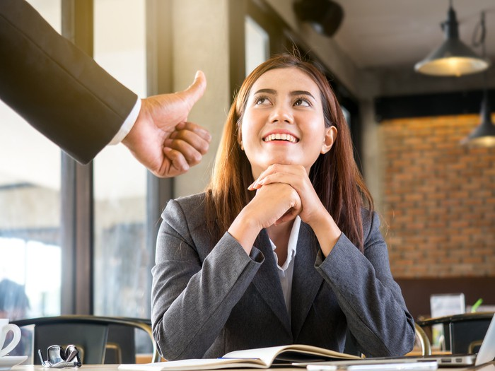 Man giving a thumbs up to a business woman sitting at a desk