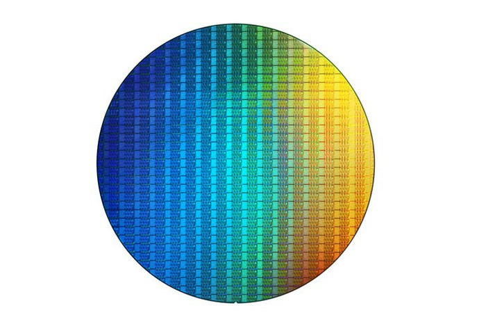 A wafer of Intel processors colored blue, green, and yellow from right to left.