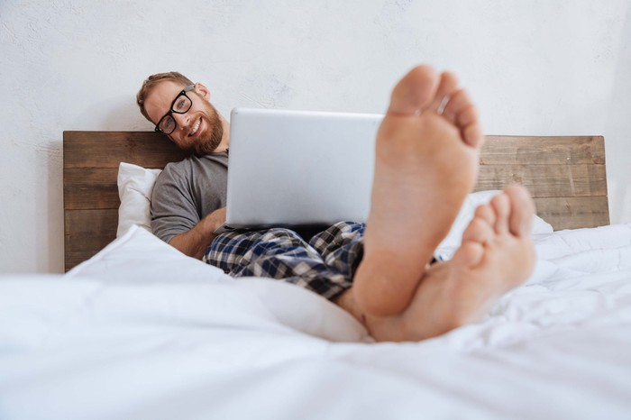 Young man in pajamas in bed with laptop on lap