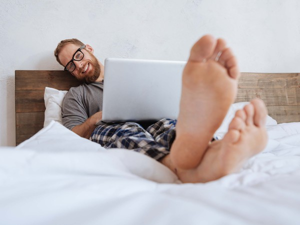 young man in pajamas in bed with laptop on lap_GettyImages-698026044