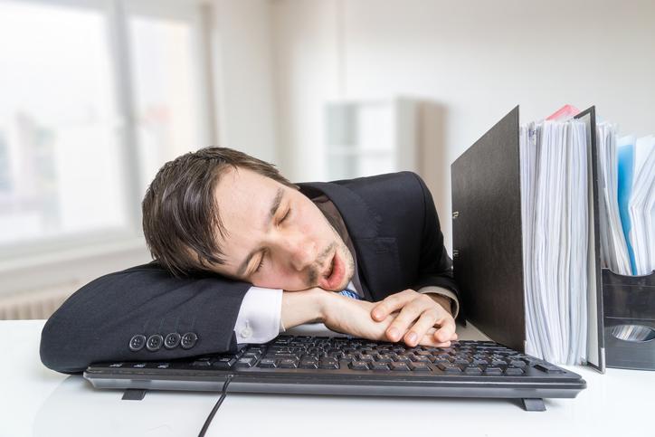 A businessman sleeping at his desk.