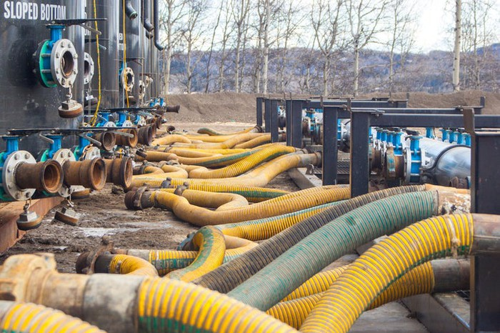 Frack sand rigs with hoses, situated at a rig.