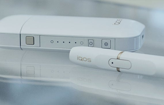 A picture of IQOS, a white charging box and a white tube that acts as the device the user inhales.