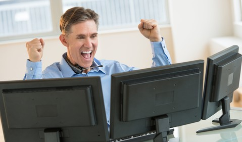 Investor at a computer looking happy -- GettyImages-460937279