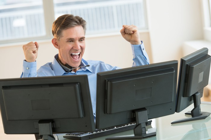 Investor at a computer looking happy