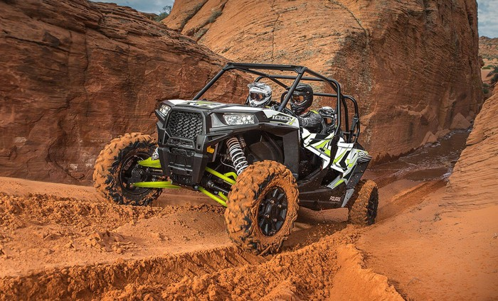 Polaris RZR 1000 driving through a dirt canyon
