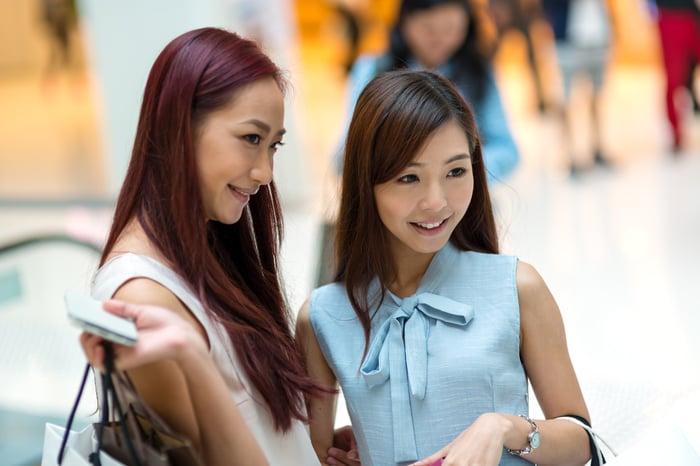 Two young women go shopping.