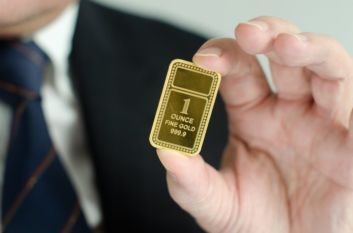 A man in a suite holding up a gold ingot