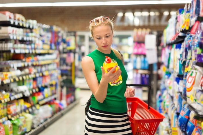 Woman in cleaning supply aisle in store, examining a bottle of dish soap