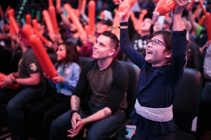 A child cheering among a crowd fans at Overwatch League event at Blizzard Arena.