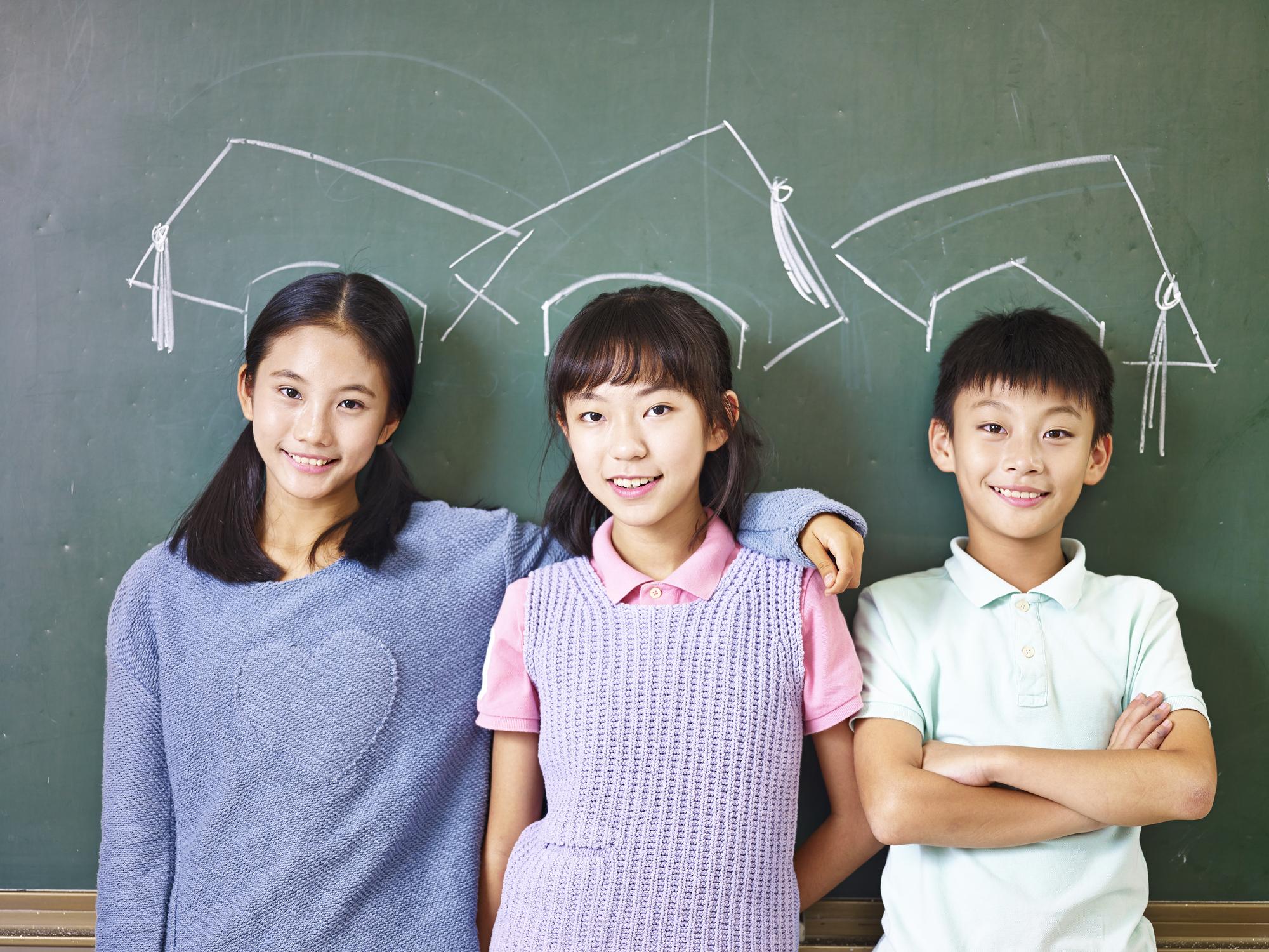 Three Asian elementary school children standing in front of chalkboard underneath chalk-drawn mortarboards