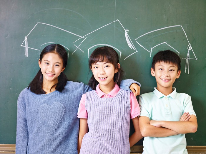 Three Asian elementary school children standing in front of chalkboard underneath chalk-drawn mortarboards