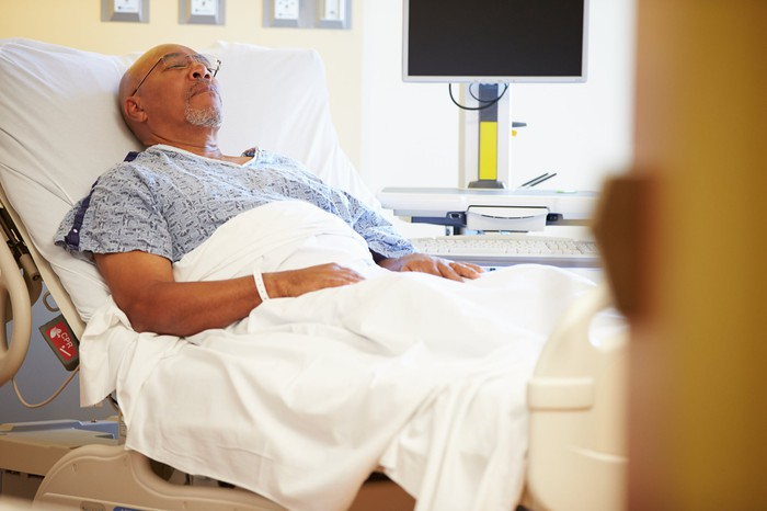 Senior man in sleeping in a semi-reclined hospital bed