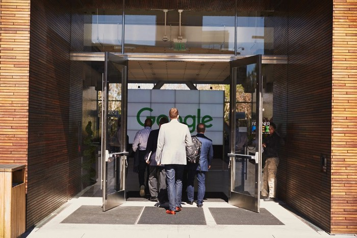 People in suits walking into Google's headquarters entrance.
